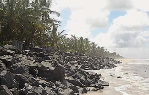 Enrocamento protegendo residências da ação erosiva das ondas na praia de São Domingos